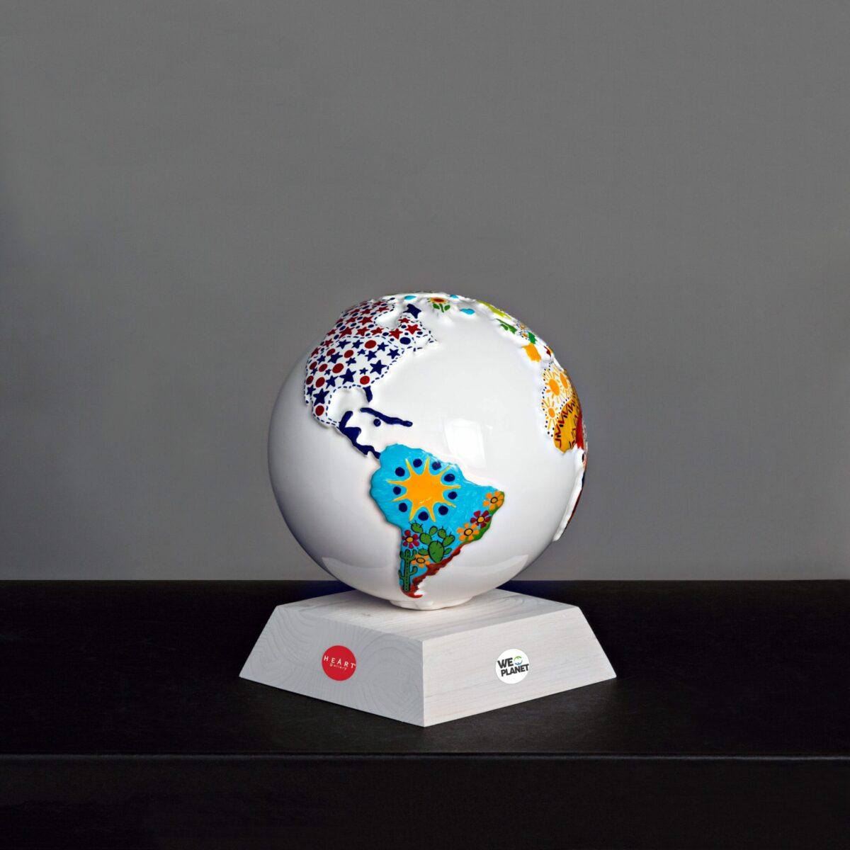 mappamondo in ceramica bianco con decori colorati sui continenti e appoggiato su una base di legno bianca
