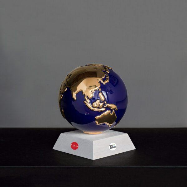 sfera in ceramica blu rappresentante il pianeta terra con i continenti smaltati in oro