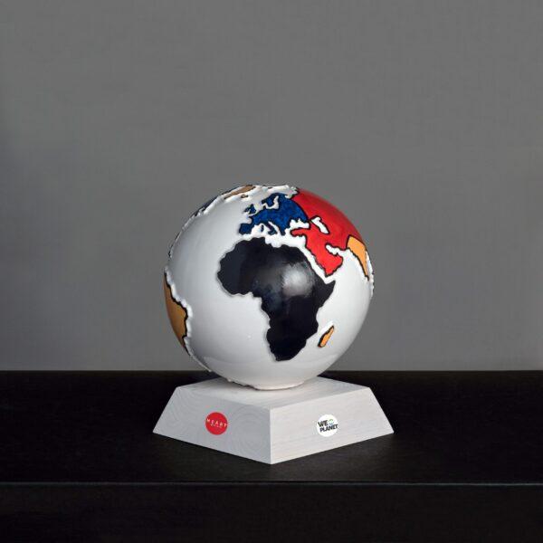 mappamondo in ceramica bianco con i continenti colorati in rosso, giallo, blu e nero secondo lo stile Mondrian