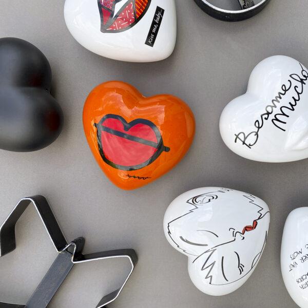 cuore tridimensionale arancio con grafica Callatelaboca