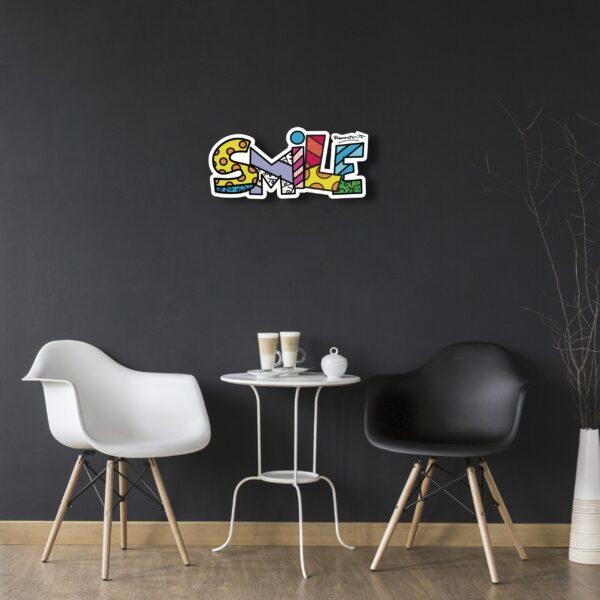scritta Smile in dibond con caratteri tutti colorati appesa su una parete nera sopra un tavolino da caffè con due sedie