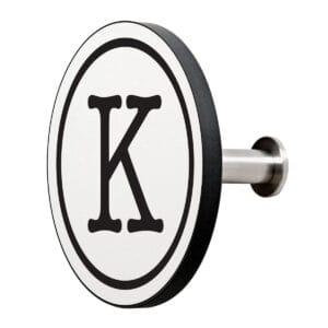 Appendiabiti a forma circolare della collezione Art-Up Alphabet con pomello in acciaio inox e appendiabiti HPL sfondo bianco lettera nera K
