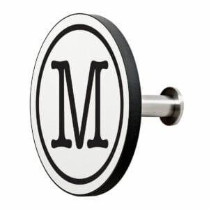 Appendiabiti a forma circolare della collezione Art-Up Alphabet con pomello in acciaio inox e appendiabiti HPL sfondo bianco lettera nera M