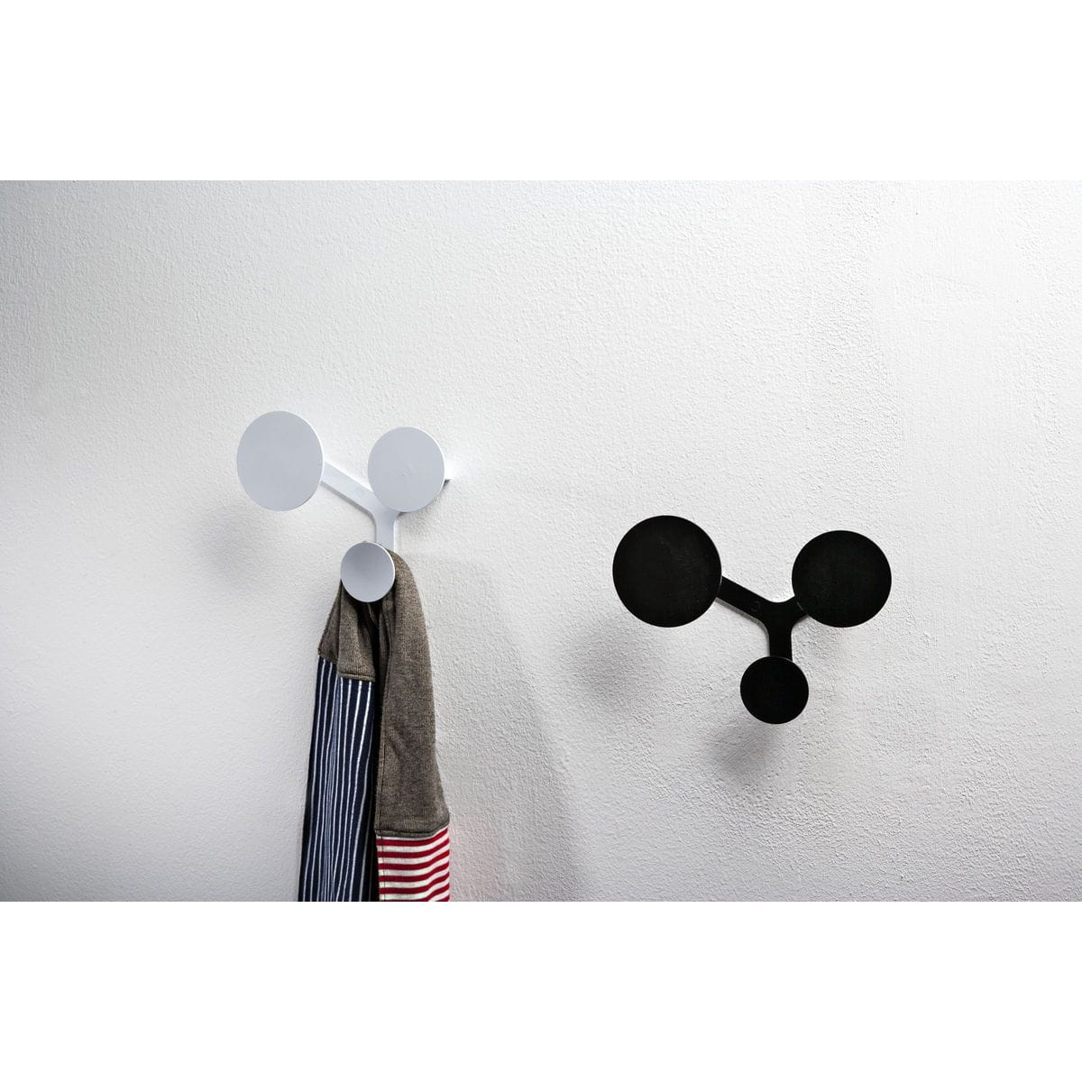 Appendiabiti a muro di metallo composto da tre dischi circolari montati sul medesimo supporto di colore bianco e nero