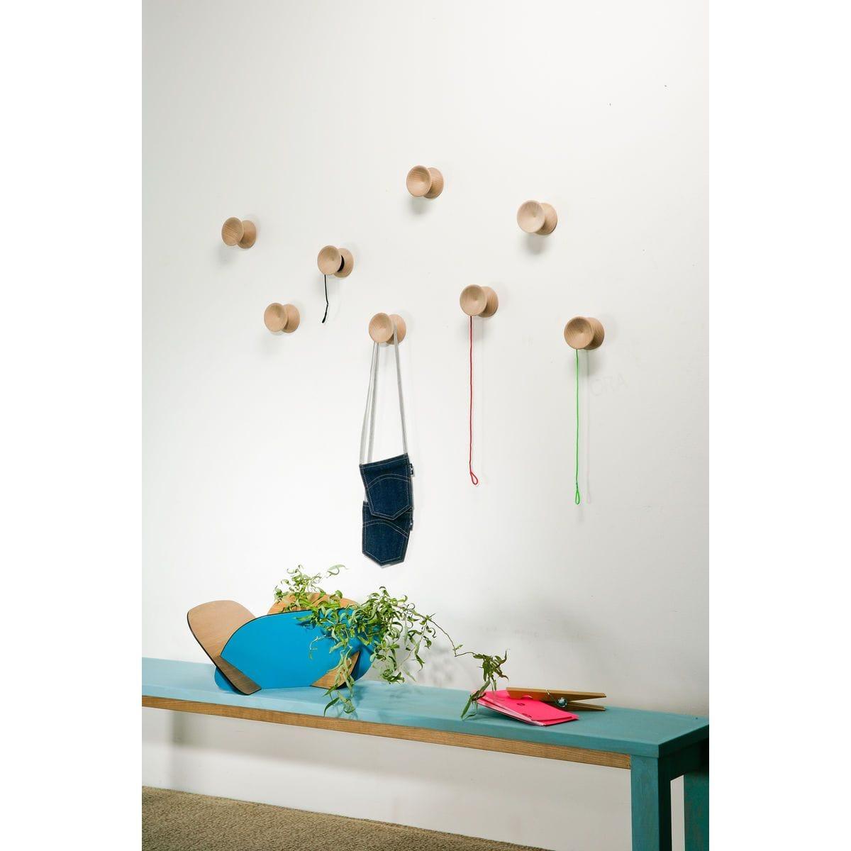 ganci appendiabiti da muro in legno a forma di yo-yo su parete bianca