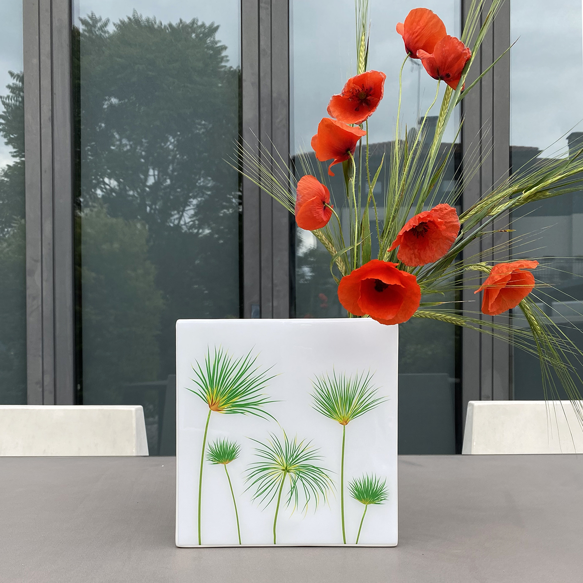 vaso design bianco raffigurante dei papiri con dei papaveri all'interno