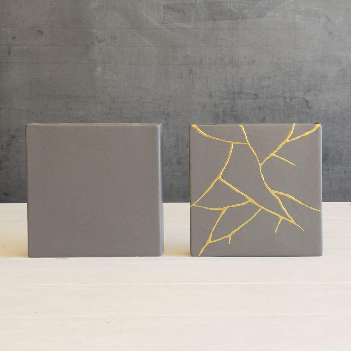 ci sono due vasi quadrati in simil cemento uno dei quali presenta delle venature dorate sulla superficie