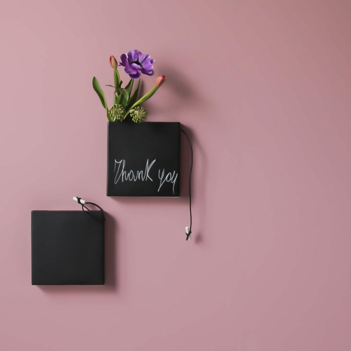due vasi quadrati neri effetto lavagna sono appesi ad una parete color rosa