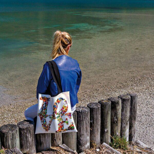 ragazza con giacca blu seduta su uno steccato con in spalla una borsa Tote Bag in bianco con scritta LOVE