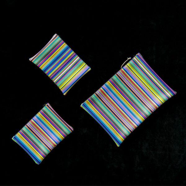 tre astucci di diverse dimensioni, di forma rettangolare, realizzati con tessuto a righe colorate disposti uno accanto all'atro.