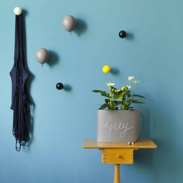 parete azzurra decorata con appendiabiti a forma di palloncino grigio e con diversi pomelli appendiabiti in ordine sparso