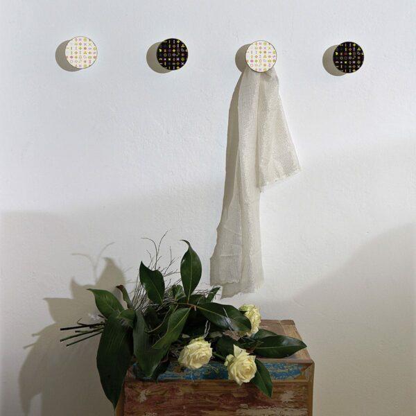 Appendiabiti a forma circolare della collezione Art-Up con pomello in acciaio inox e appendiabiti HPL con grafica colorata su sfondo bianco o nero di Karim