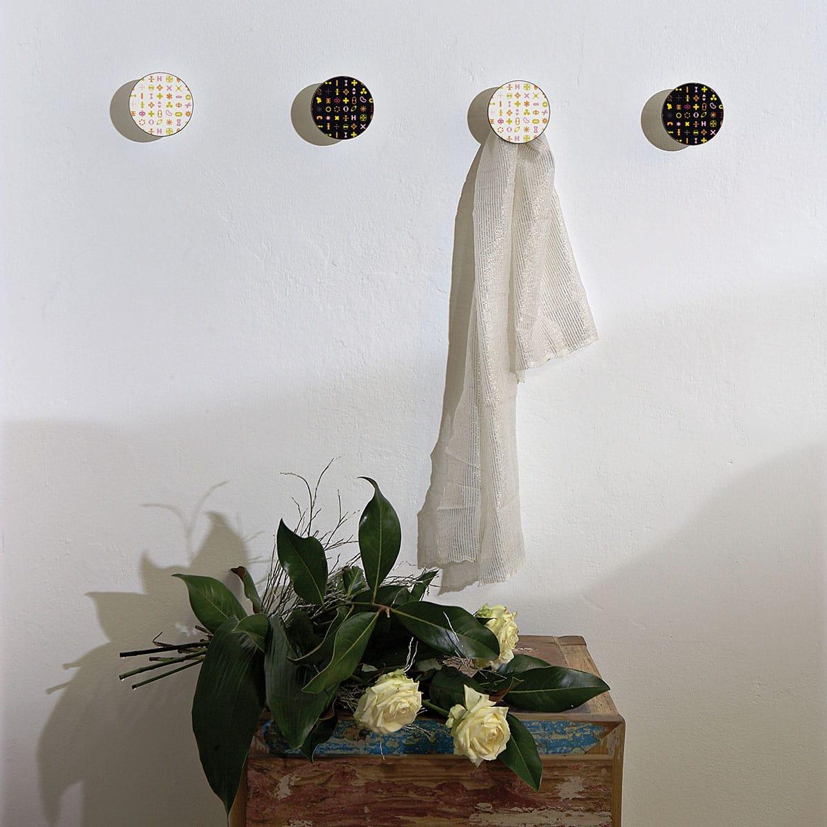 Appendiabiti a forma circolare della collezione Art-Up con pomello in acciaio inox e appendiabiti HPL con grafica colorata su sfondo bianco e Nero di Karim