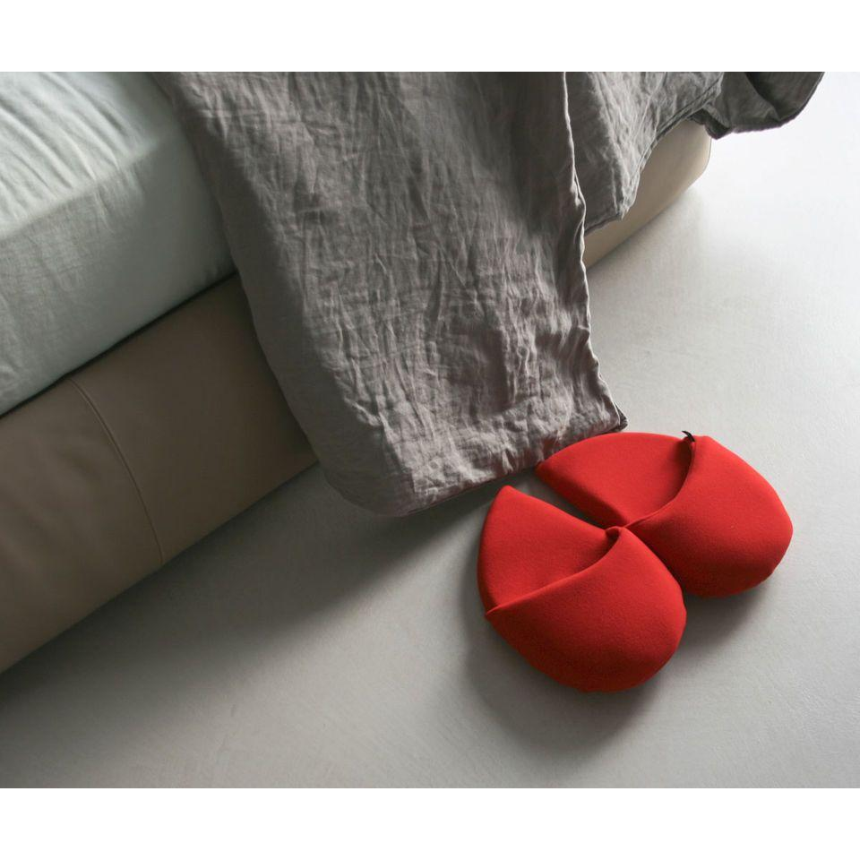 ciabatte in pile a forma di cuore ai piedi di un letto
