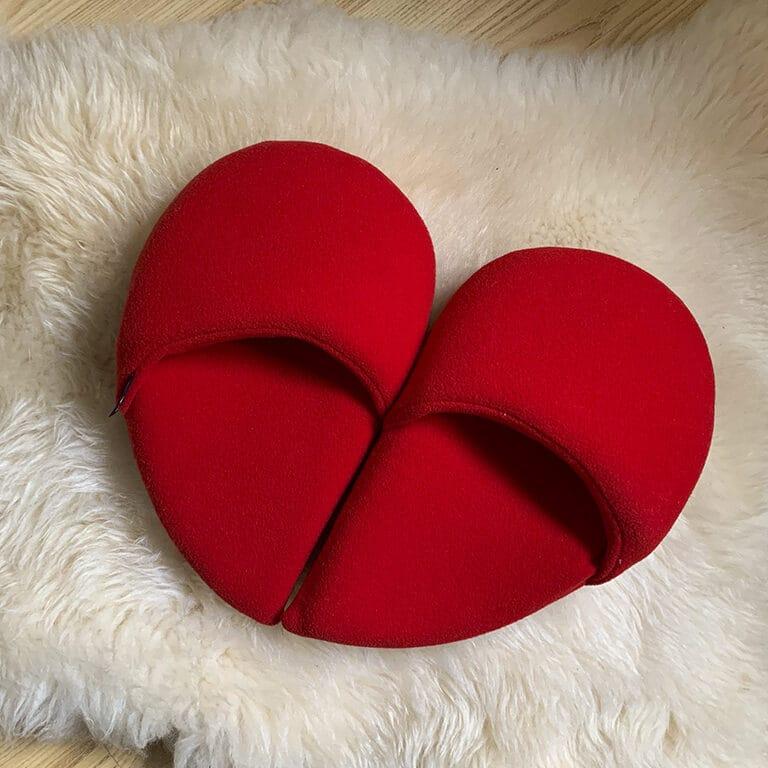 ciabatte realizzate in pile rosso, unite formano un cuore, ogni piede calza mezzo cuore