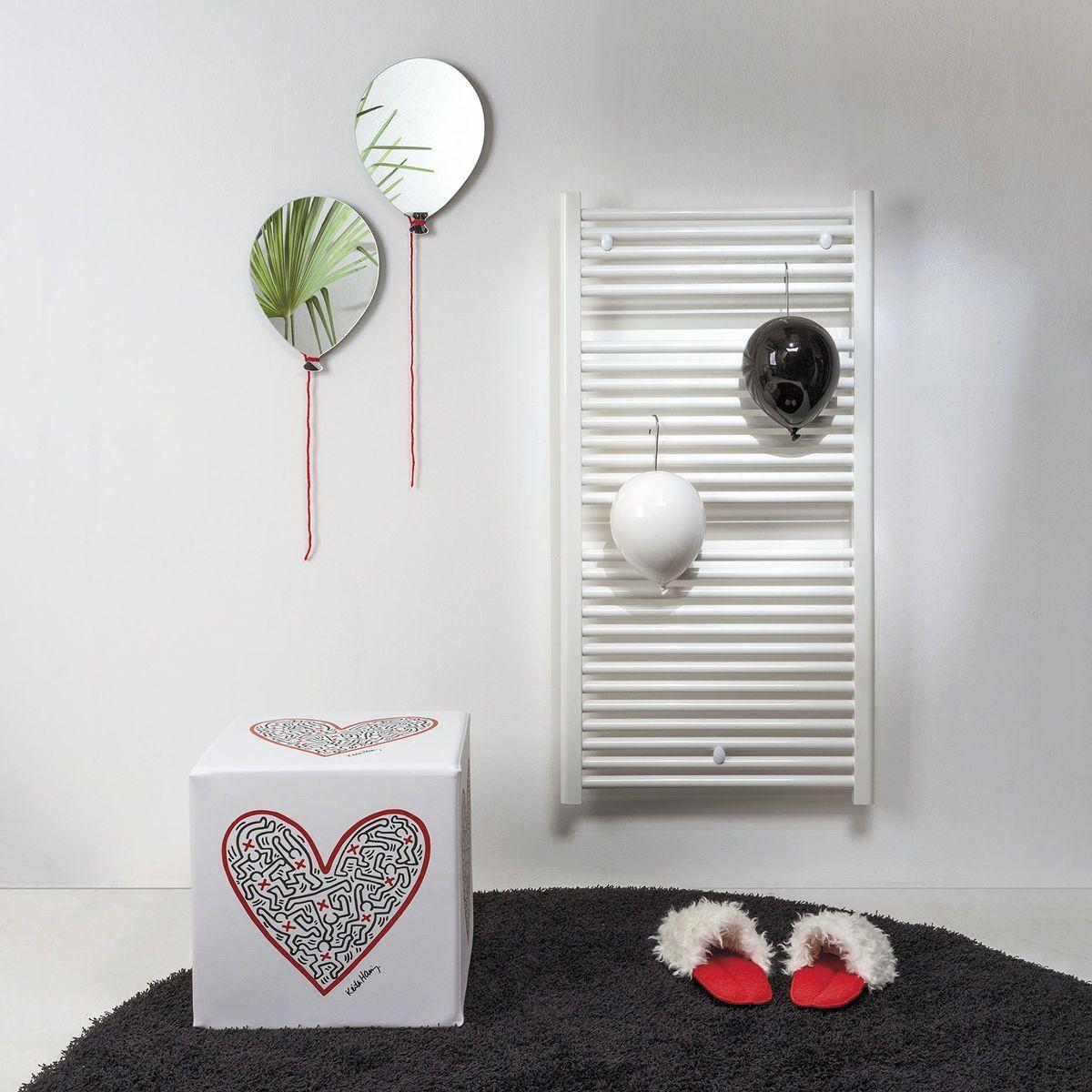 ciabatte da camera in pile rosso e pelliccia bianca Pelù su tappeto nero ai piedi di un radiatore bianco e accanto a un pouf bianco