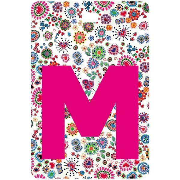 Etichetta bagaglio con lettera alfabeto bianca su sfondo fantasia cuori e fiori colorati con iniziale M