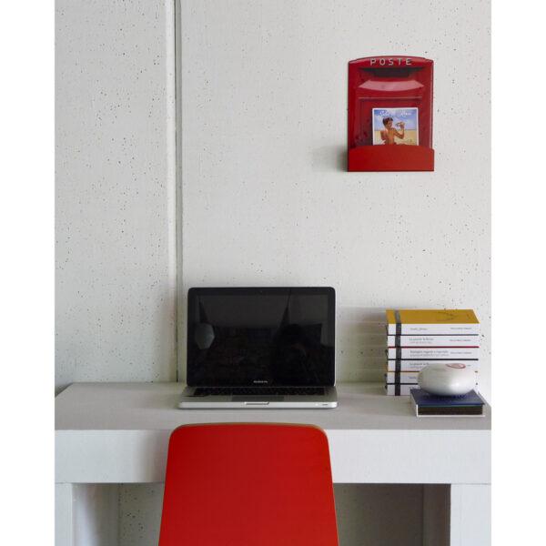 scrivania con computer e porta lettere appesa al muro a forma di cassetta postale italiana in miniatura