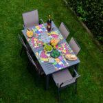 una tavola in giardino è apparecchiata con 6 tovagliette americane quadrate che riportano le immagini di Romero Britto