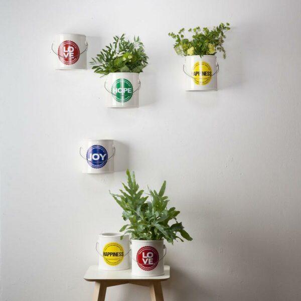 vasi in ceramica bianchi simili ai barattoli di vernice appesi alla parete con piante all'interno