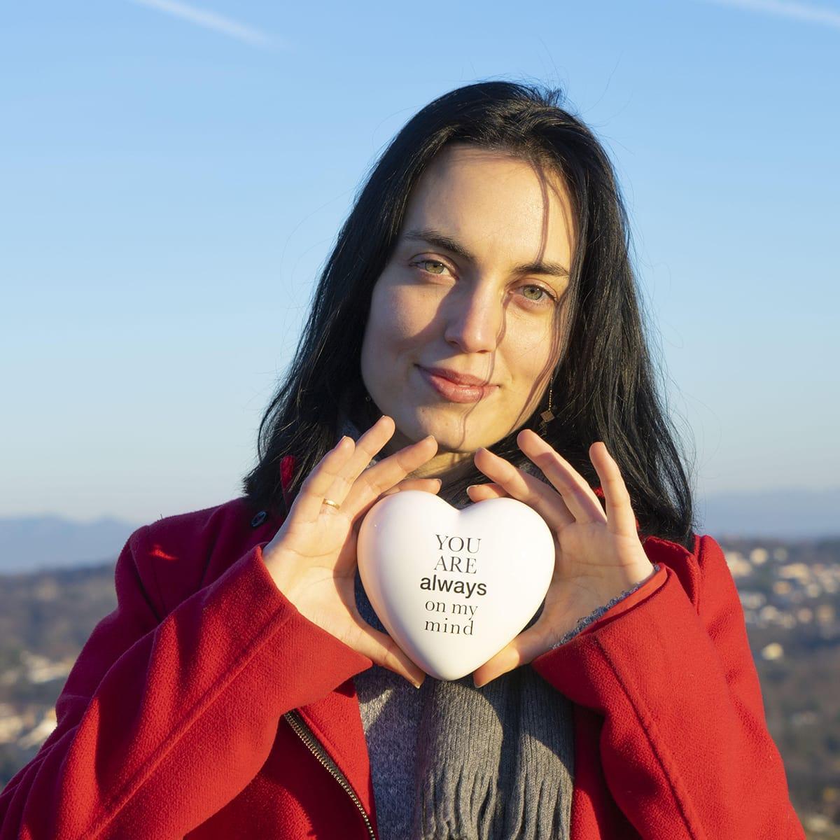 una ragazza tiene tra le mani un cuore in ceramica bianco con la scritta you are always on my mind