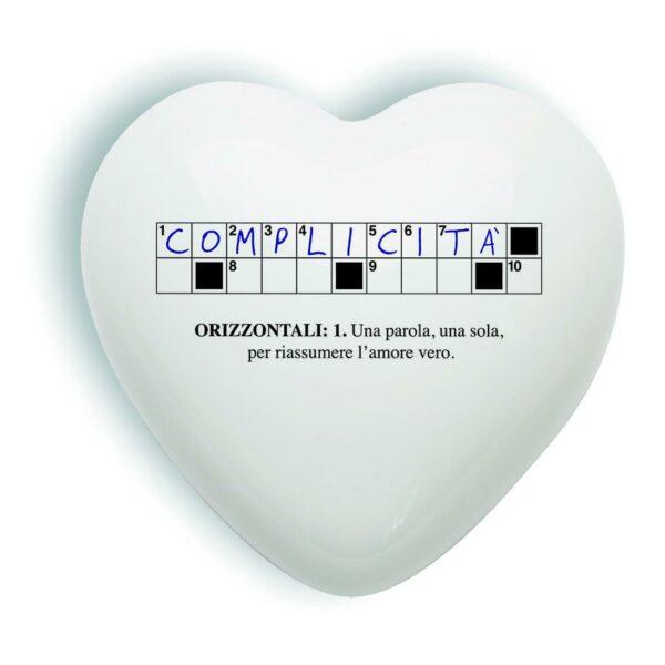 cuore tridimensionale in ceramica bianca raffigurante due righe di un cruciverba e la definizione di complicità