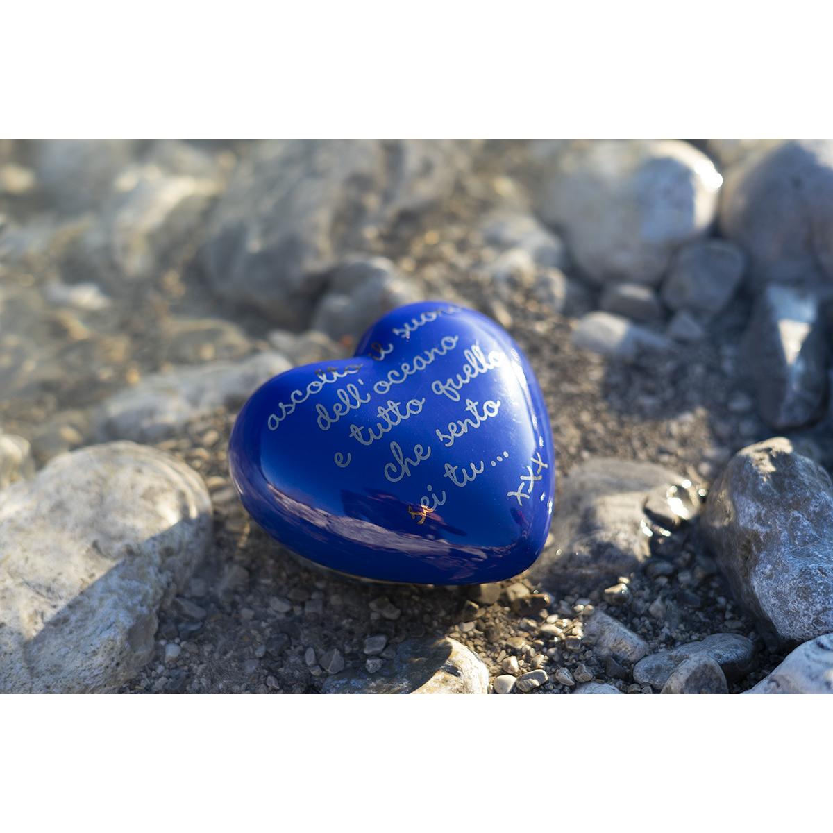 su un cuore tridimensionale blu c'è scritta una poesia d'amore legata agli oceani