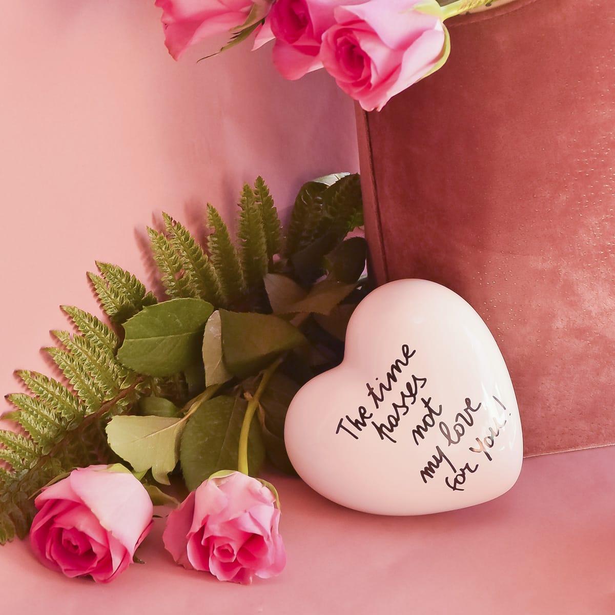 cuore in ceramica bianco con frase romantica in inglese accanto ad una borsa piena di rose rosa