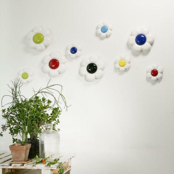 margherite in ceramica bianca con pistillo colorato di due grandezze diverse disposte in ordine sparso su una parete bianca
