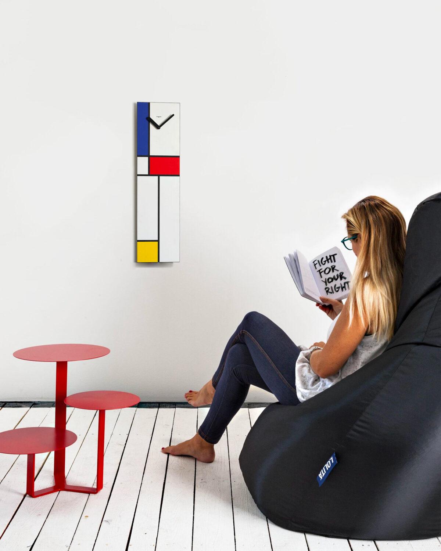 su una parete bianca cattura l'attenzione un orologio verticale ispirato alle geometrie e i colori di Mondrian.