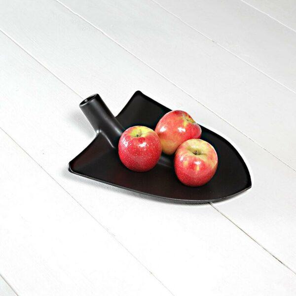 su un tavolo bianco è usato come porta frutta la testa di una pala nera realizzata in ceramica
