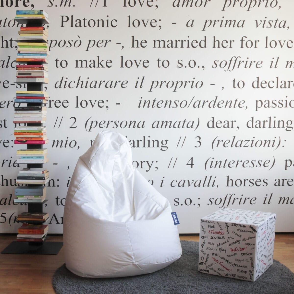 un pouff quadrato con la stampa su tutti i lati di parole relative all'amore fà da poggiapiedi o tavolino ad una poltrona a sacco bianca