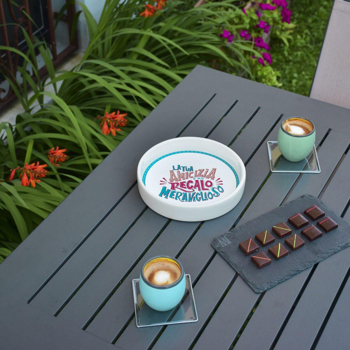 """ciotola in ceramica con scritta """"la tua amicizia è un regalo meraviglioso"""" è al centro di un tavolo con due tazzine di caffè e cioccolatini"""