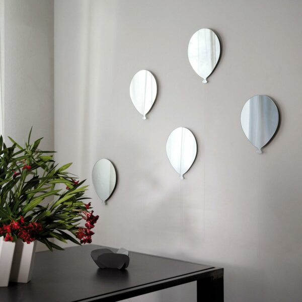 un bouquet di 5 palloncini in vetro formano una composizione di specchi su una parete bianca. I palloncini sono rifiniti anche con un filo bianco