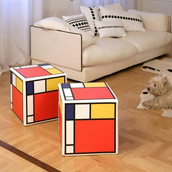 due pouf a cubo rigidi con stampa ispirazione Mondrian su ogni lato con il rosso colore dominante seguito dal giallo, blu e bianco, nero
