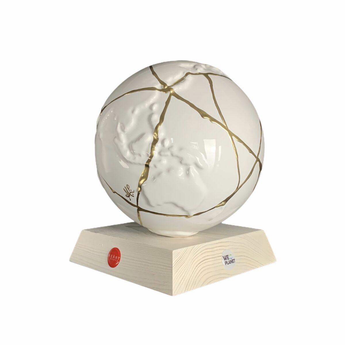 oggetto decorativo a forma di pianeta terra bianco rotto e riparato con venature dorate kintusugi