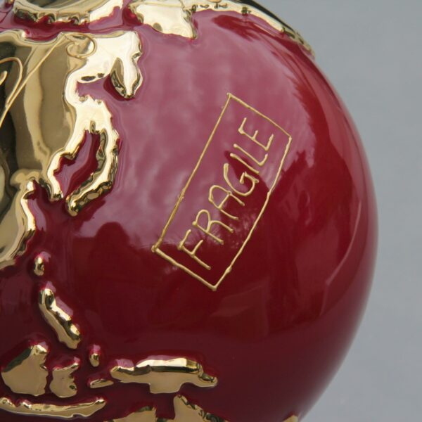 """particolare globo in ceramica rosso rappresentante la terra con la scritta """"Fragile"""" dorata"""