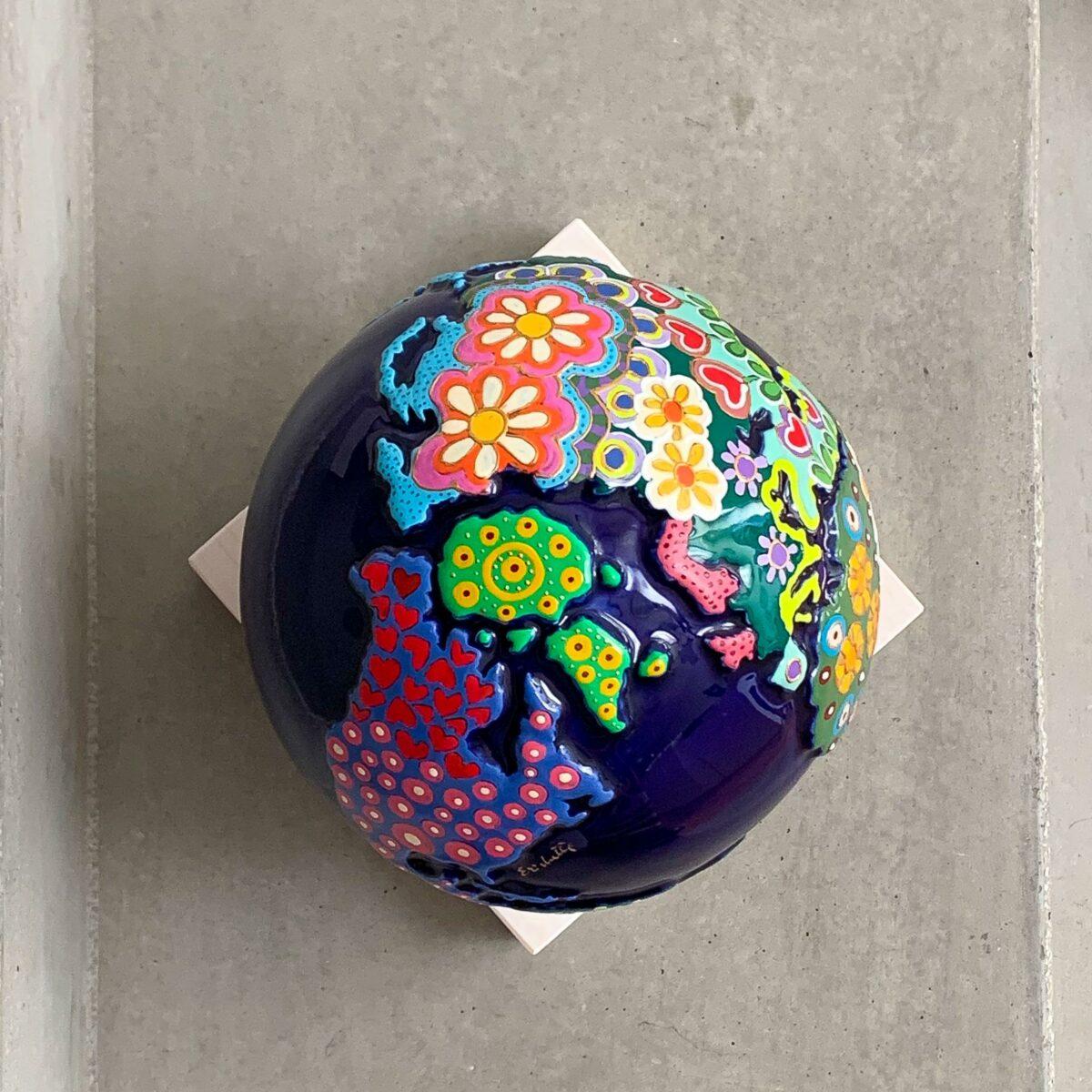 globo in ceramica blu rappresentante la terra con decori a mano sui continenti e appoggiato su una base quadrata in legno bianco