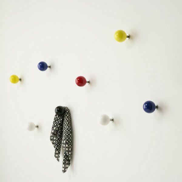palline appendiabiti in ceramica colorata appese in ordine sparso su una parete bianca