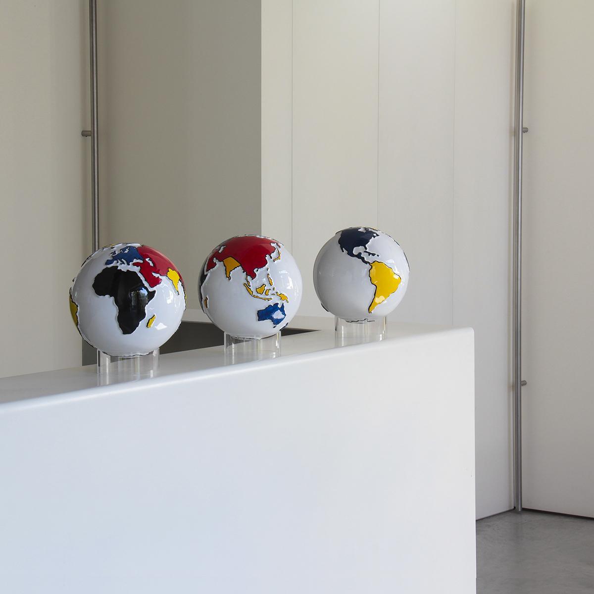 sul bancone della reception sono disposti 3 mappamondi in ceramica decorati con i colori secondo lo stile Mondrian