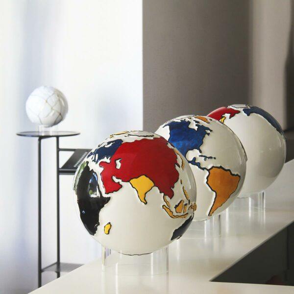 un globo in ceramica bianco rappresenta la terra e le terre emerse sono dipinte secondo lo stile Mondrian