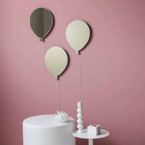 3 specchi in vetro a forma di palloncino e con un cordoncino bianco sono appesi su una parete di colore rosa antico sopra ad un pouf e un tavolino bianco