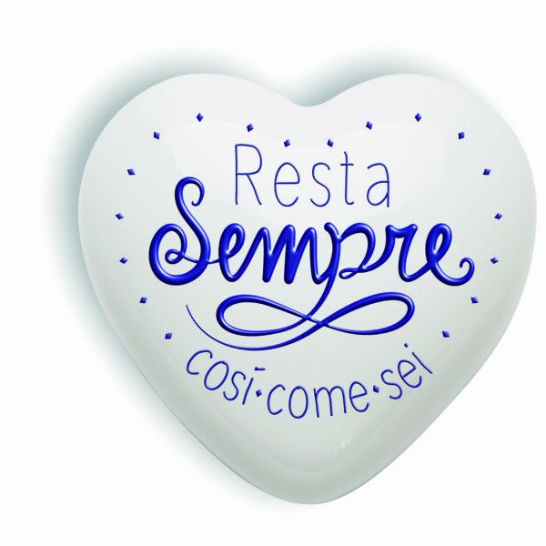 """messaggio positivo """"resta sempre così come sei"""" scritto in blu su un cuore in ceramica bianco"""