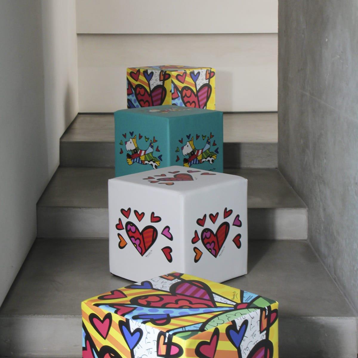 alcuni pouf cubici colorati disposti ad altezze diverse su una scala