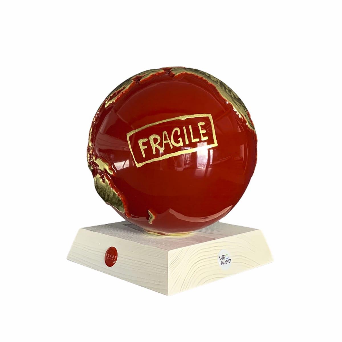 """il pianeta terra realizzato in ceramica smaltata: di rosso gli oceani, in oro i continenti e una scritta """"fragile"""""""