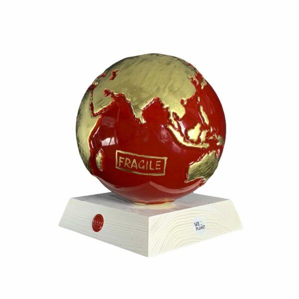 il pianeta terra realizzato in ceramica smaltata di rosso e in oro sono dipinte a mano le terre emerse e la scritta fragile