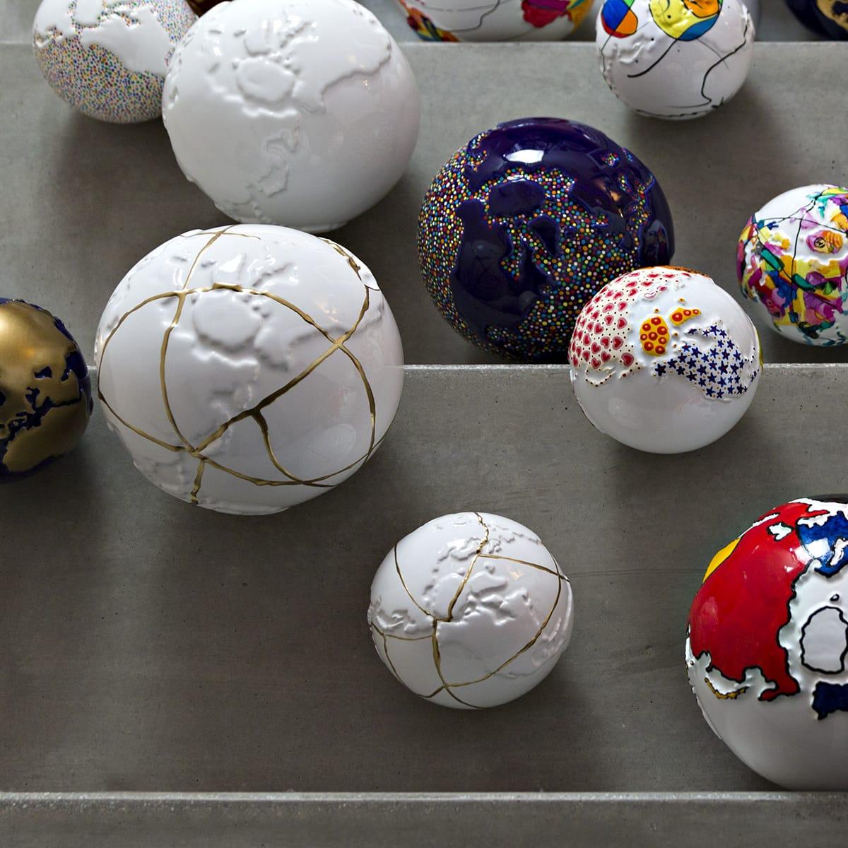 sfere in ceramica a forma di pianeta terra decorate con l'oro kintsugi