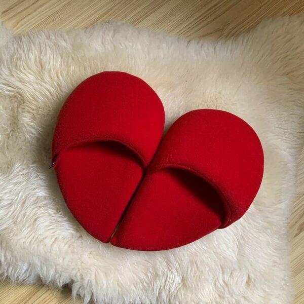 ciabatte in morbido pile rosso a forma di cuore.