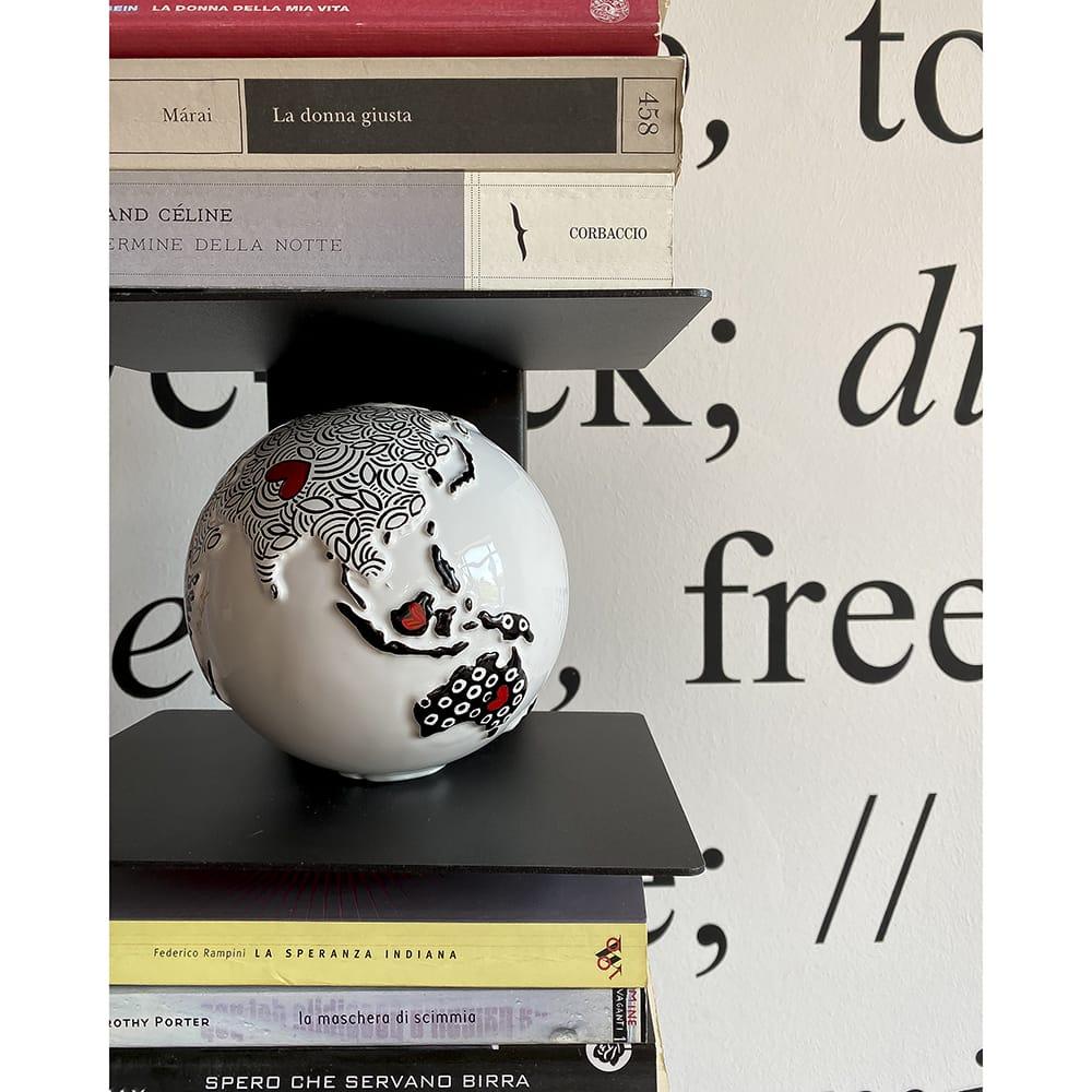 mappamondo design dipinto a mano in bianco e nero appoggiato su uno scaffale di una libreria