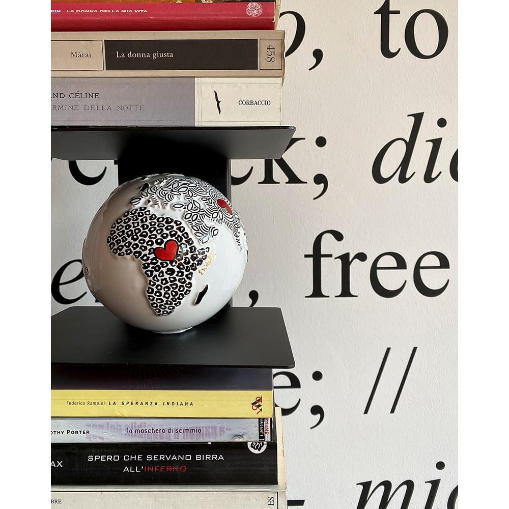 mappamondo artistico bianco e nero appoggiato tra i libri